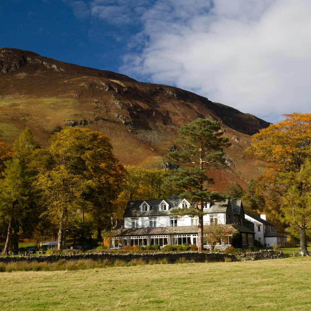 White painted, grey roofed hotel seen across field, autumn trees around, mountain behind