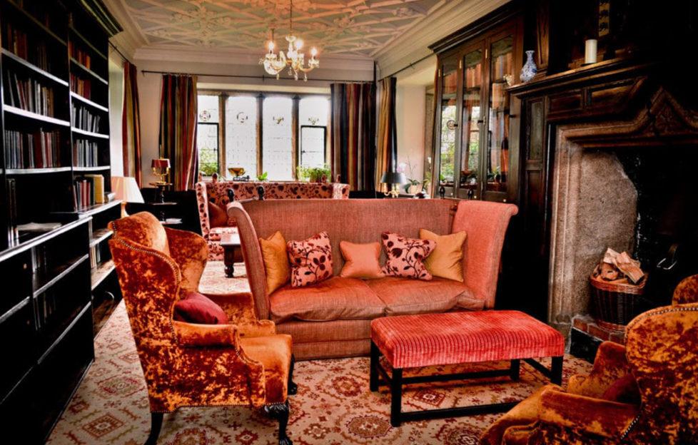 The drawing room at Lewtrenchard Manor, dark wood, mullioned window and orange velvet sofas