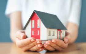 Lady holding a model house in her hands Pic: Istockphoto