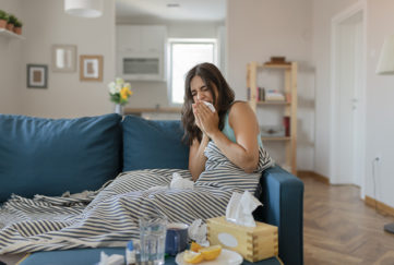 Sick Woman Covered With a Blanket Lying in Bed With High Fever and a Flu, Resting at Living Room. She is Exhausted and Suffering From Flu. Sick Woman With Runny Nose Lying in Bed. Girl Suffering From Cold Lying in Bed With Tissue Blowing Her Nose While Sitting on the Sofa