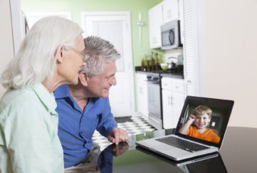 A senior couple use a laptop computer at home to video-chat with their grandson.