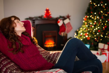 Pretty redhead resting on the armchair at christmas at home in the living room