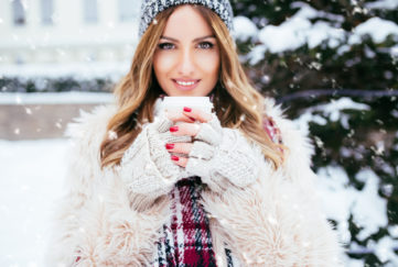 Winter portrait of beautiful woman holding a coffee to go outside on winter, snowy day.