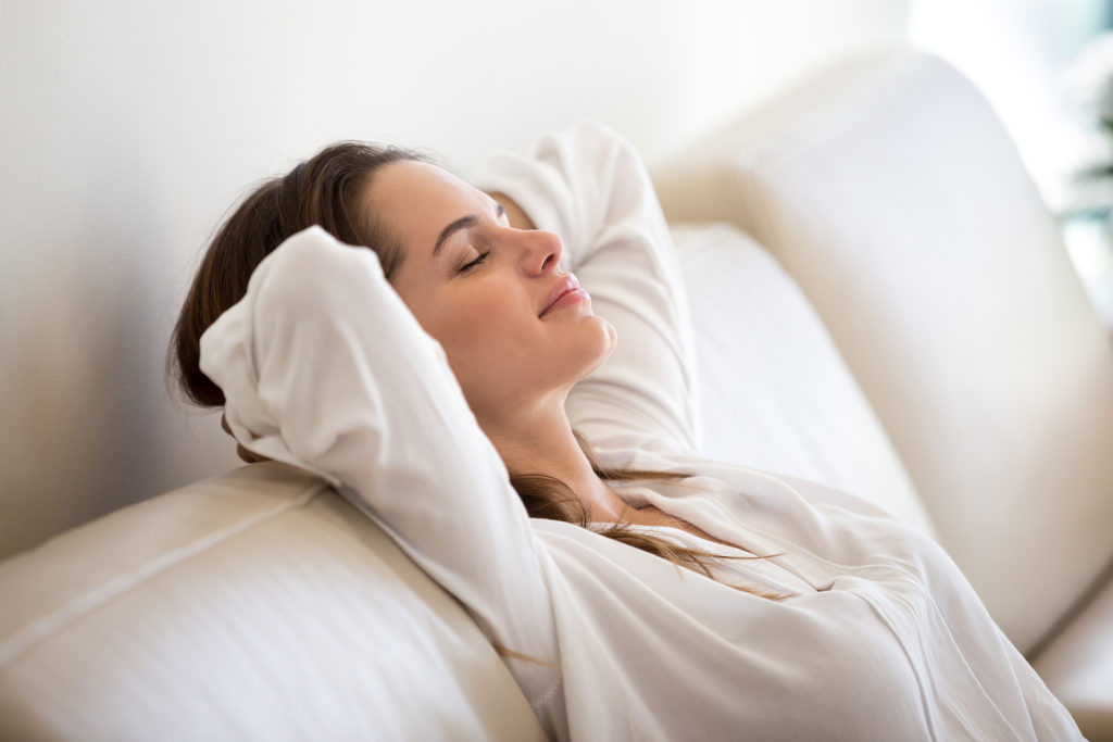 Calm millennial woman relaxing on soft comfortable sofa meditating or having daytime nap, carefree lazy girl breathing fresh air enjoying no stress free peaceful weekend morning resting on couch