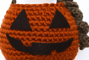 Close up of orange crocheted basket with felt features to resemble a pumpkin lantern