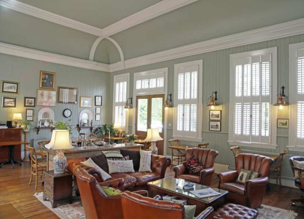 Airy room with large windows, sage green walls, leather chairs and sofas around low tables