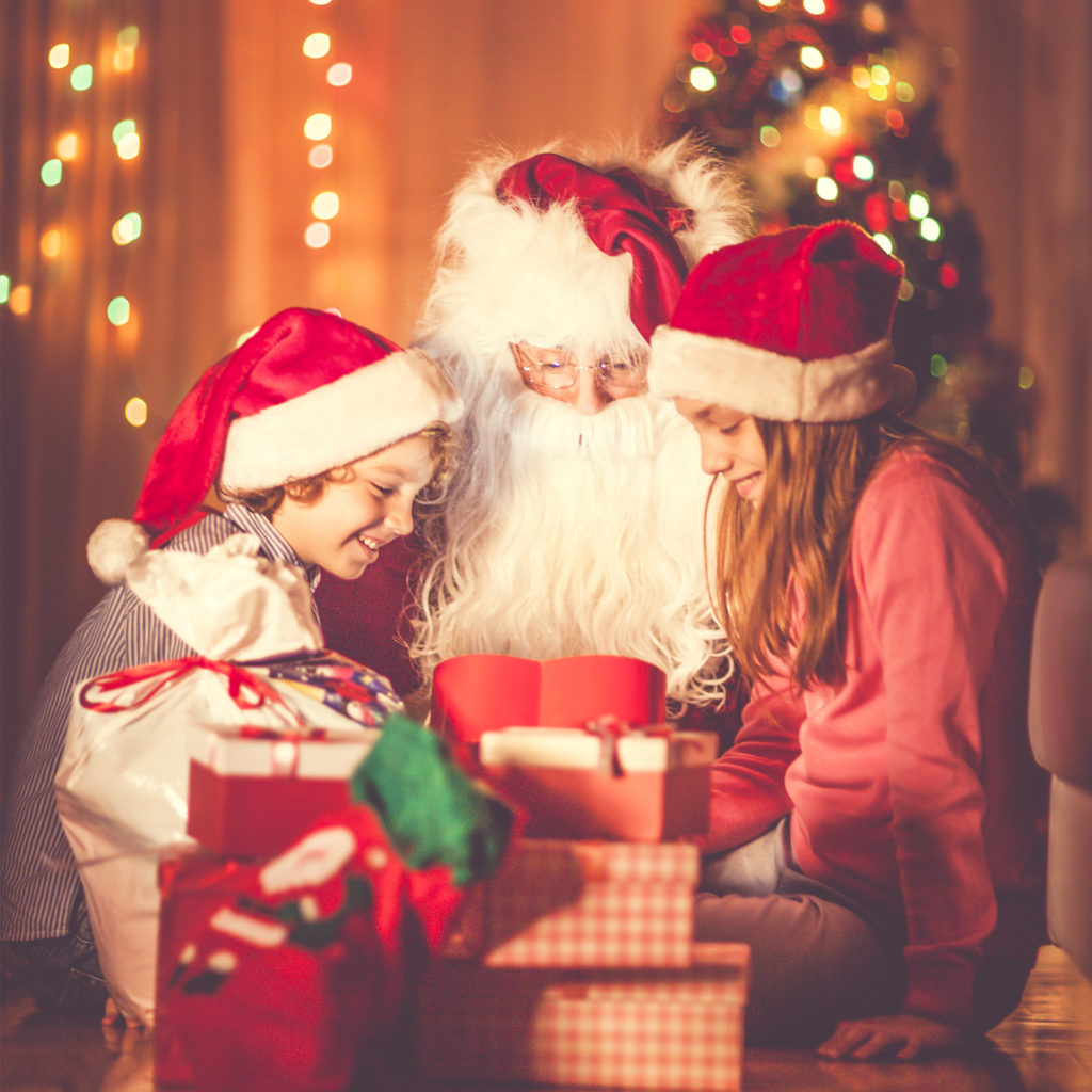 Santa watches as a boy and girl aged around 8 years, wearing Santa hats, open gift boxes, cosy surroundings with fairy lights