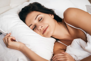 Woman sleeping peacefully in fresh white bedlinen. How to get better sleep
