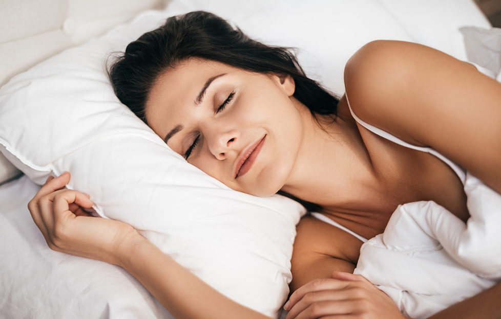 Woman sleeping peacefully in fresh white bedlinen. How to get better sleep