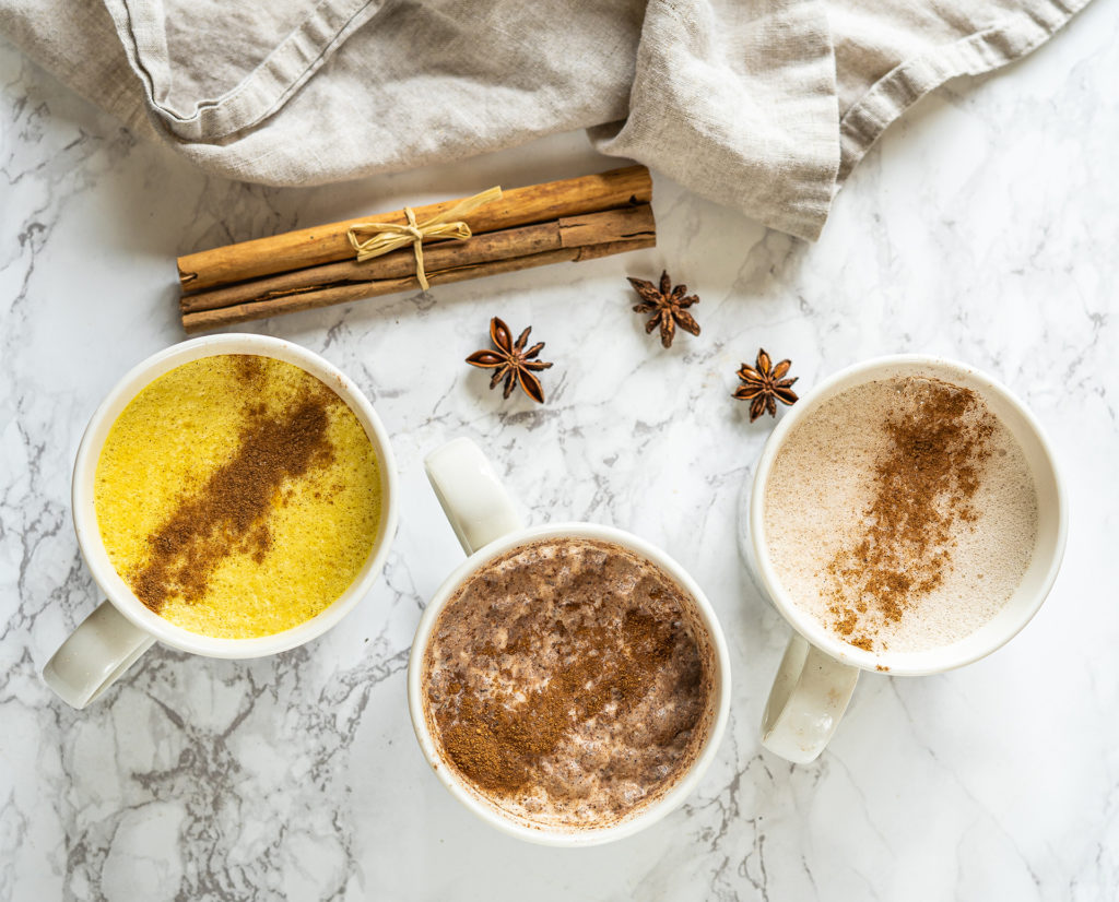 3 mugs of milk with spices sprinkled on top, cinnamon sticks and star anise to the side