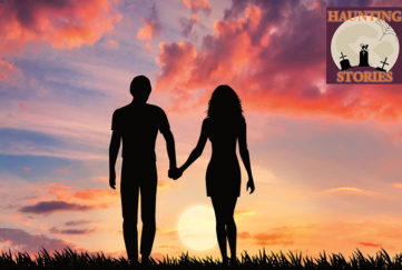Young couple holding hands silhouetted against colourful sunset sky