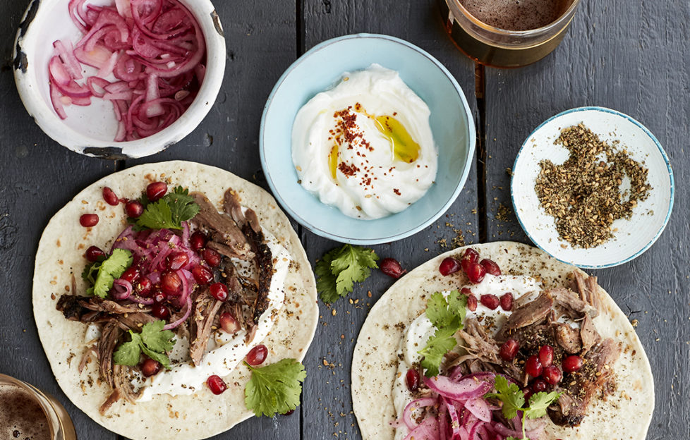 lamb tacos ready to roll up, colourful with red onion and pomegranate seeds, yogurt in a blue dish