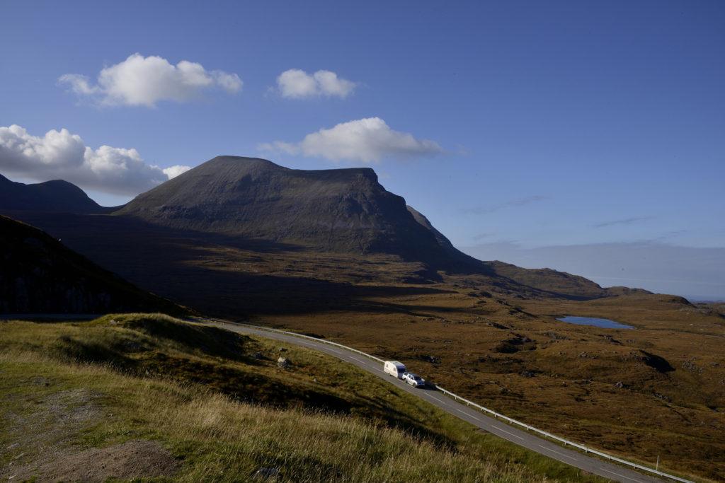 Car pulling a caravan through a mountain range