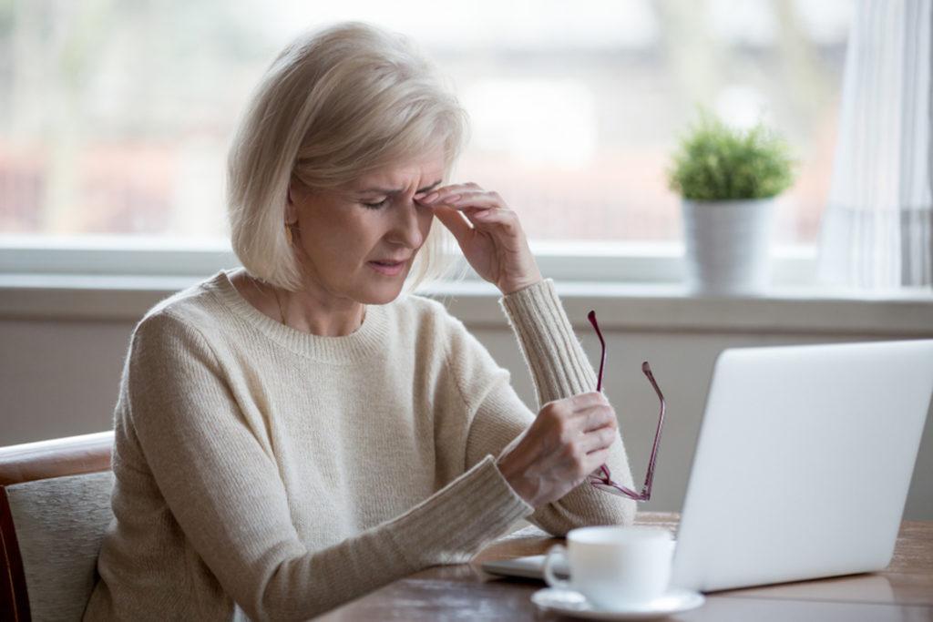 Woman sitting at laptop rubbing her eyes