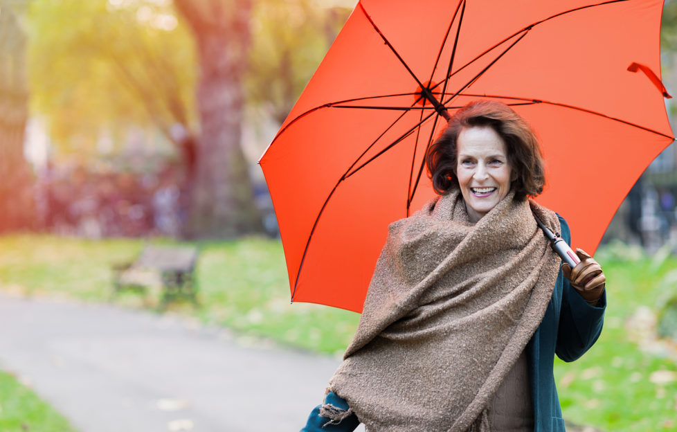 Older woman walking in the park with an orange umbrella