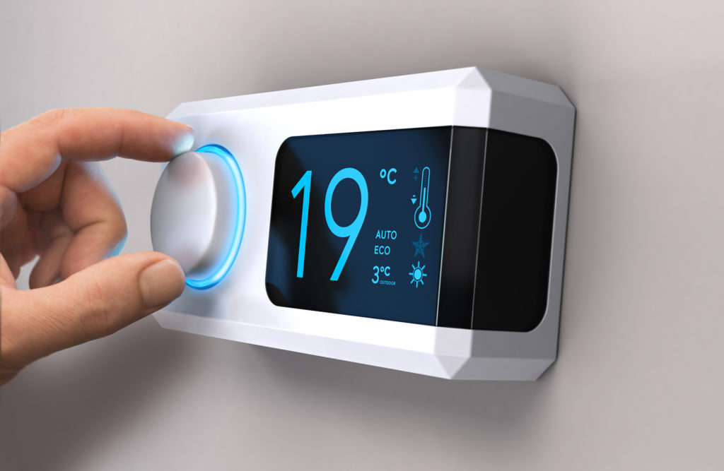 Hand turning a home thermostat knob to set temperature on energy saving mode. celcius units. Composite image between a photography and a 3D background.