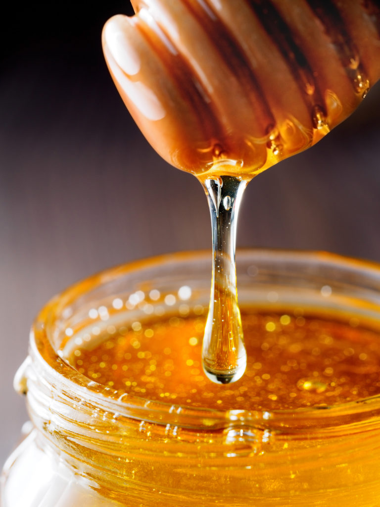 Honey dripping from honey-dipper close up