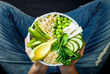 Girl in jeans holding vegan, detox green Buddha bowl with quinoa, avocado, cucumber, spinach, tomatoes, mung bean sprouts, edamame beans, daikon radish. Top view, overhead