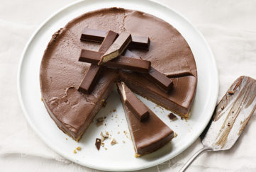 Chocolate cheesecake decorated with KitKat fingers, several slices cut