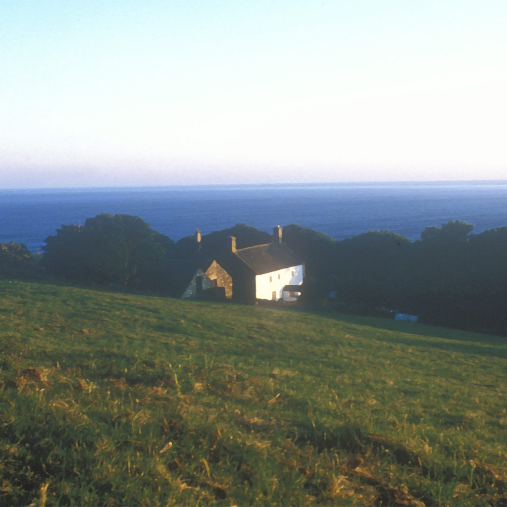 View over hillside to deep blue sea of Cardigan Bay, white painted farmhouse visible among trees