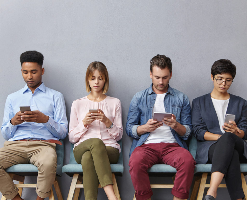 4 people all sitting and looking at their phones