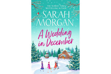 Cover of A Wedding In December. A couple and two women in wedding outfits are following a path through the snow to a log cabin. Large pine trees are decorated with lights.