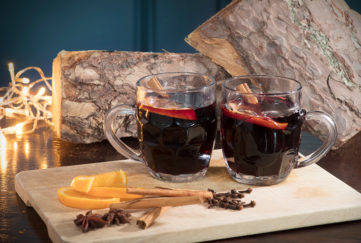 2 half pint glasses of mulled wine, dark red drink, slices of orange and spices in foreground, fairly lights and rustic log behind