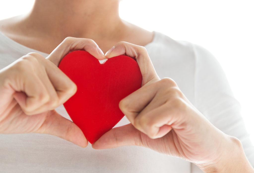 Red paper heart engulfed in fingers shaped like a heart