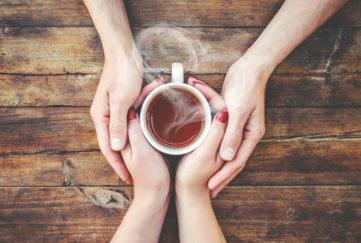 A cup of tea in the hands of a man and a woman.