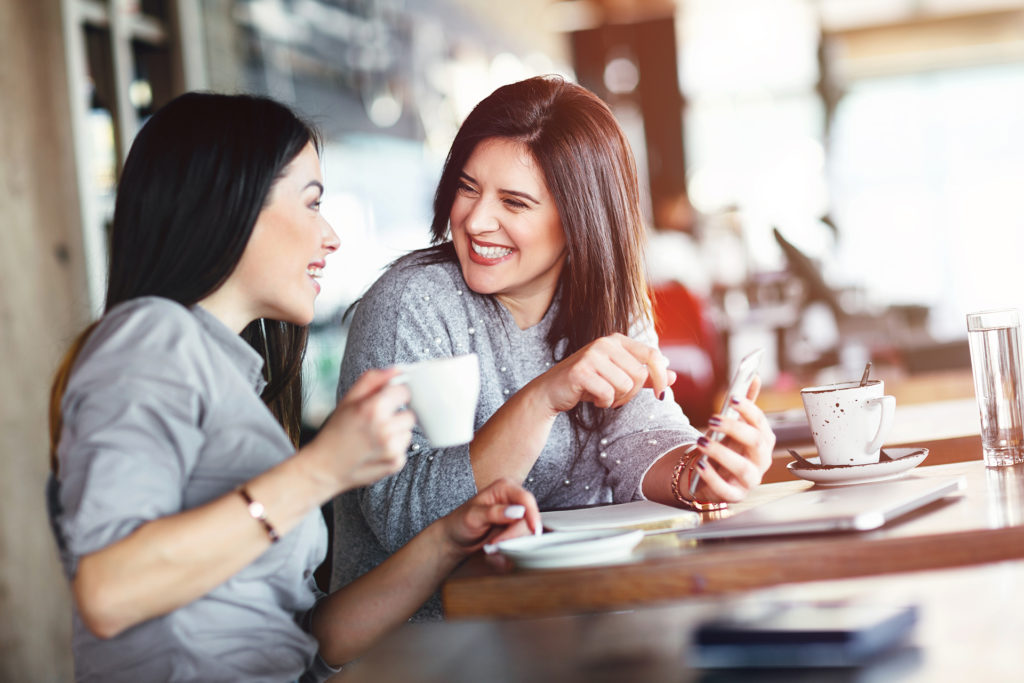 Two smiling women chatting in cafe