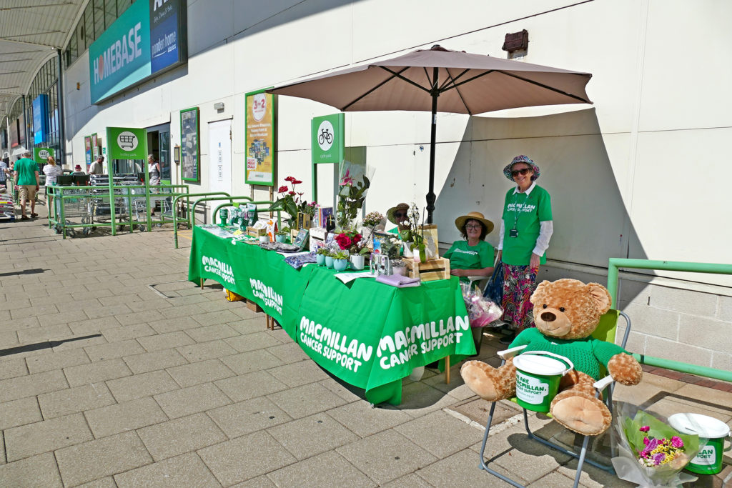 Macmillan Cancer Support. Charity stand outside superstore. Collecting money by selling china, books and cards. Three lady volunteers in uniform under white parasol.;