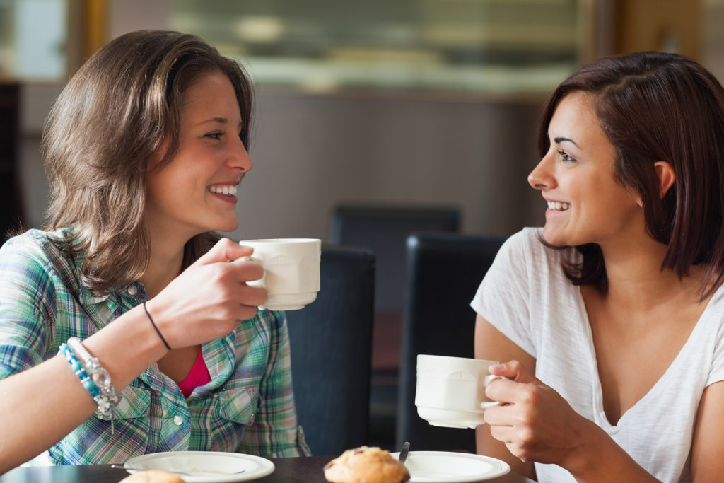 Two smiling students having a cup of coffee in college canteen.