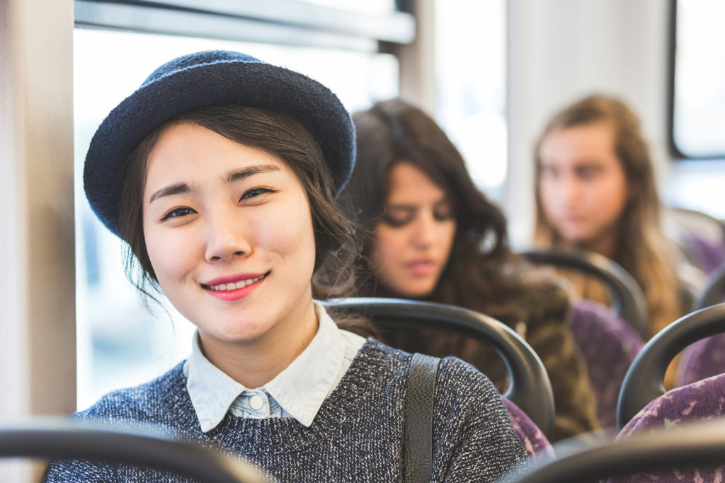 Asian lady smiling on bus
