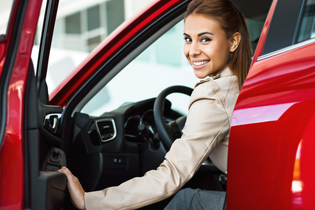 smiling woman opening door of her red car