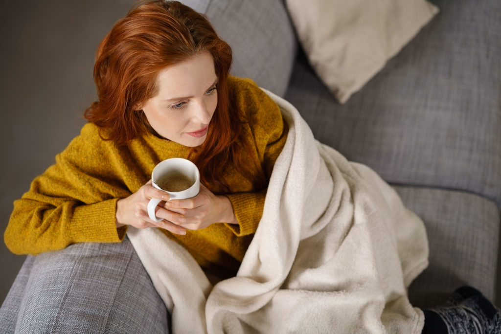 Relaxed young redhead woman enjoying a tea break sitting wrapped in a warm blanket on a comfortable couch staring thoughtfully ahead, high angle view.