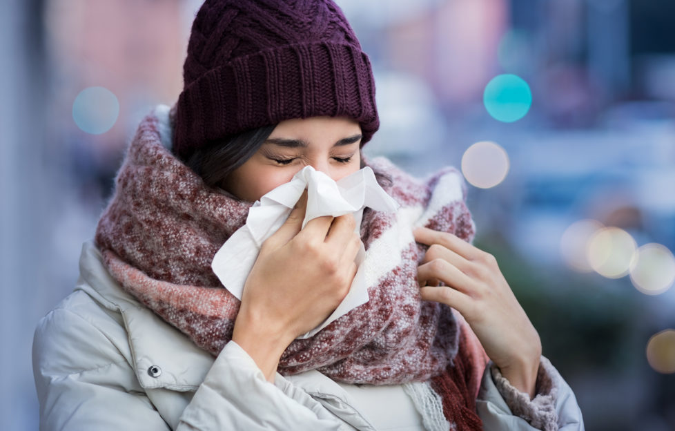 Pretty young woman blowing her nose with a tissue outdoor in winter. Young woman getting sick with flu in a winter day. Woman with a cold.;