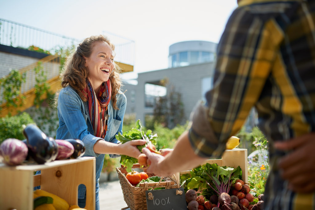 Friendly woman tending an organic vegetable stall at a farmer's market and selling fresh vegetables from the rooftop garden;