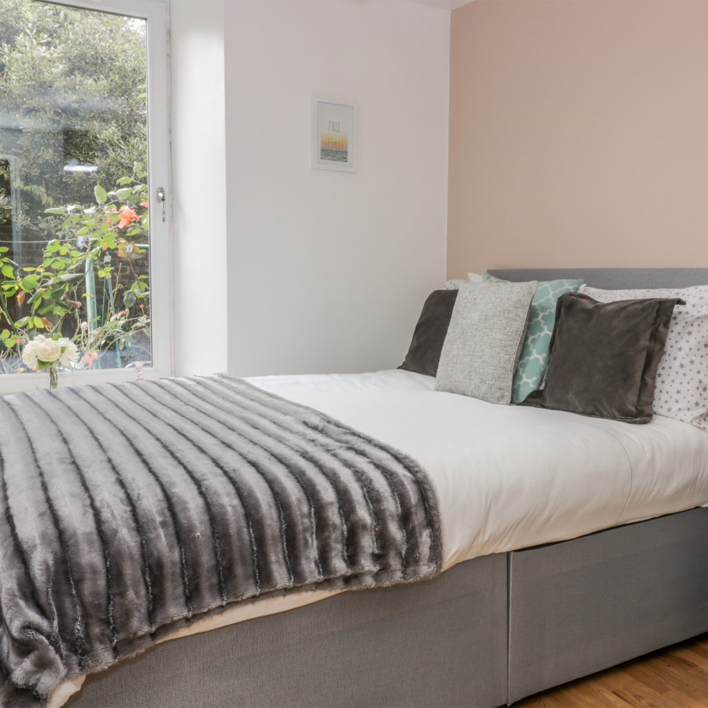 Smart, comfortable double bed by window looking on to cottage garden