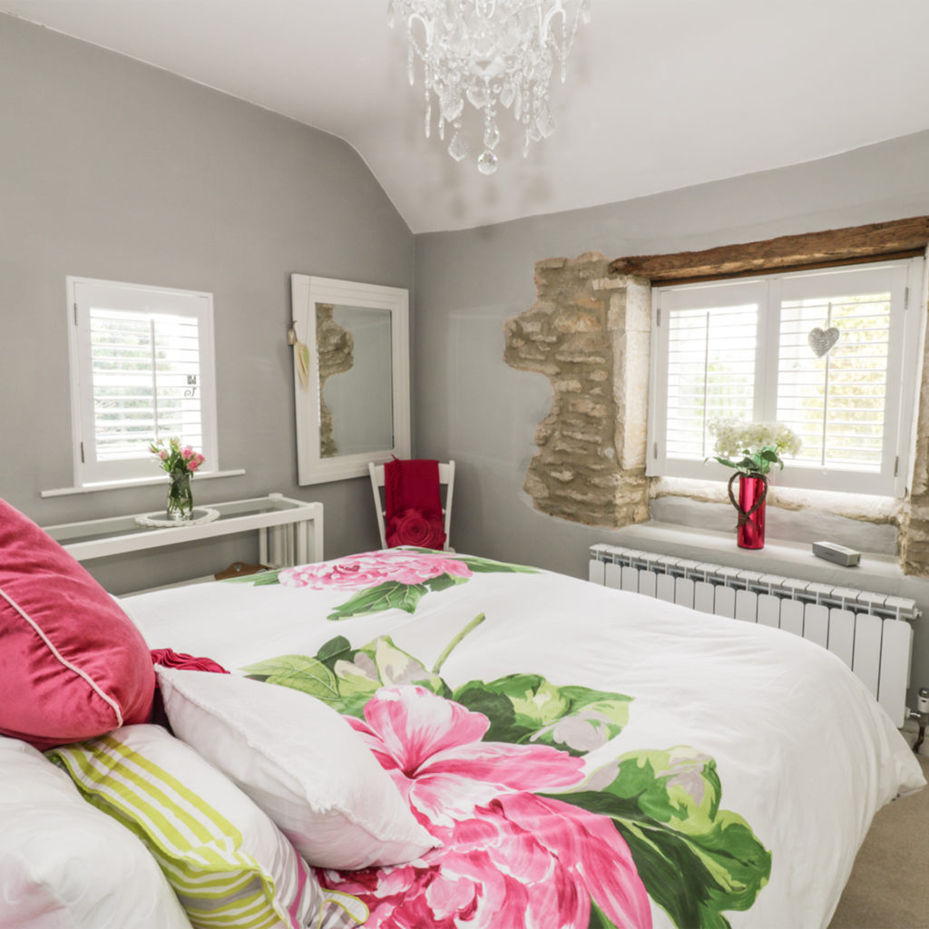 Cottage bedroom, huge bright pink flowers on bedlinen, original beam and stonework visible around window