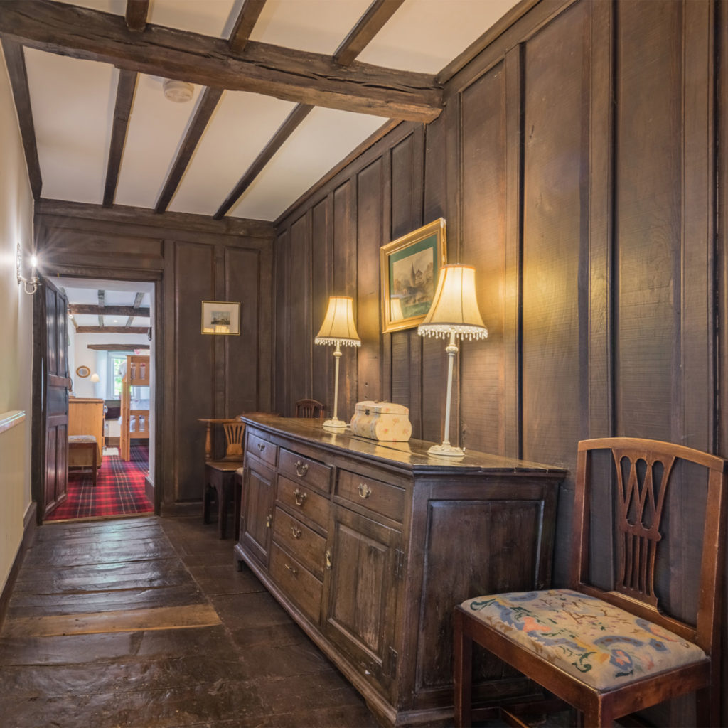 wood panelled hallway, beamed ceiling, old dresser and chairs, light bright room through doorway at the end