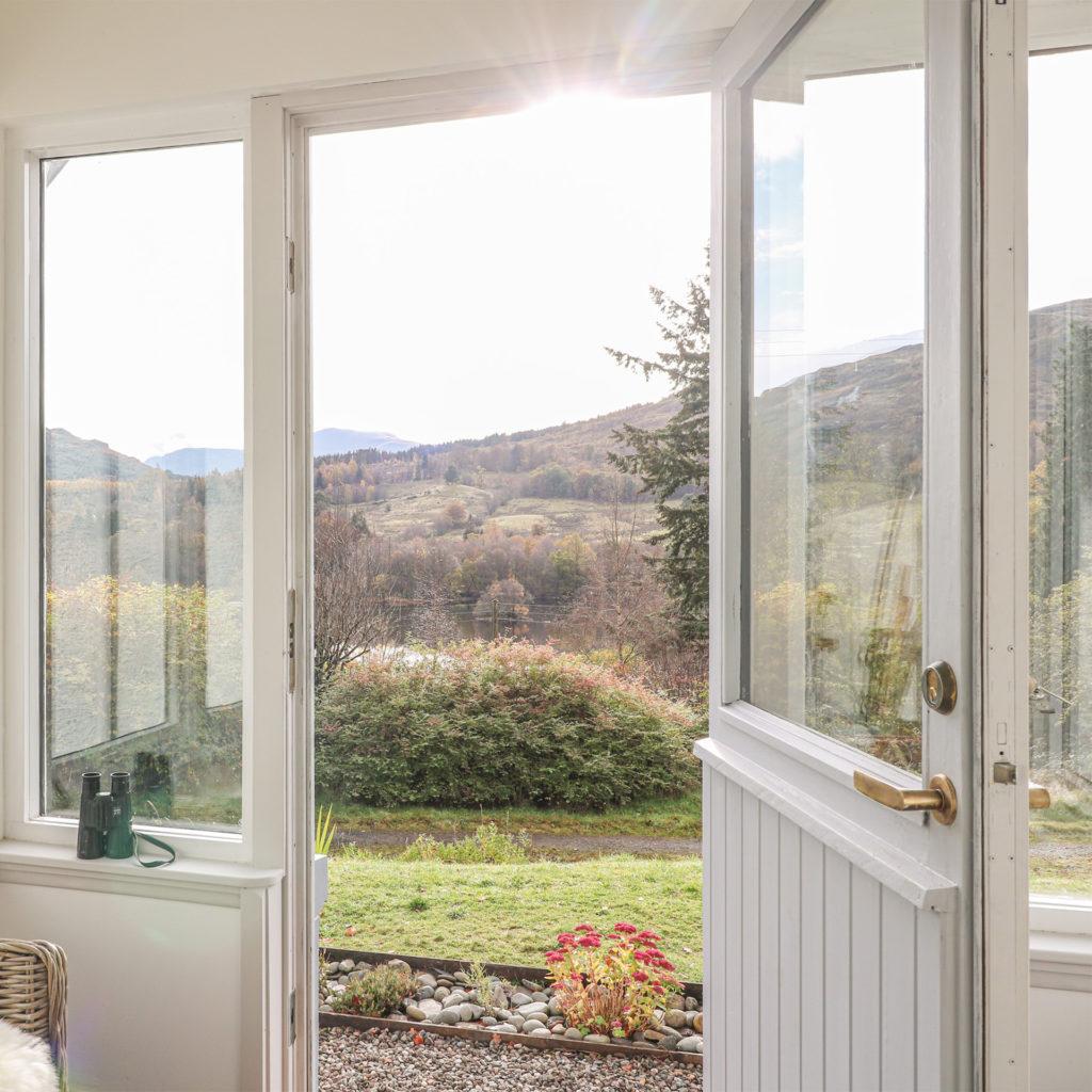 Open porch door looking out onto heather clad hillside