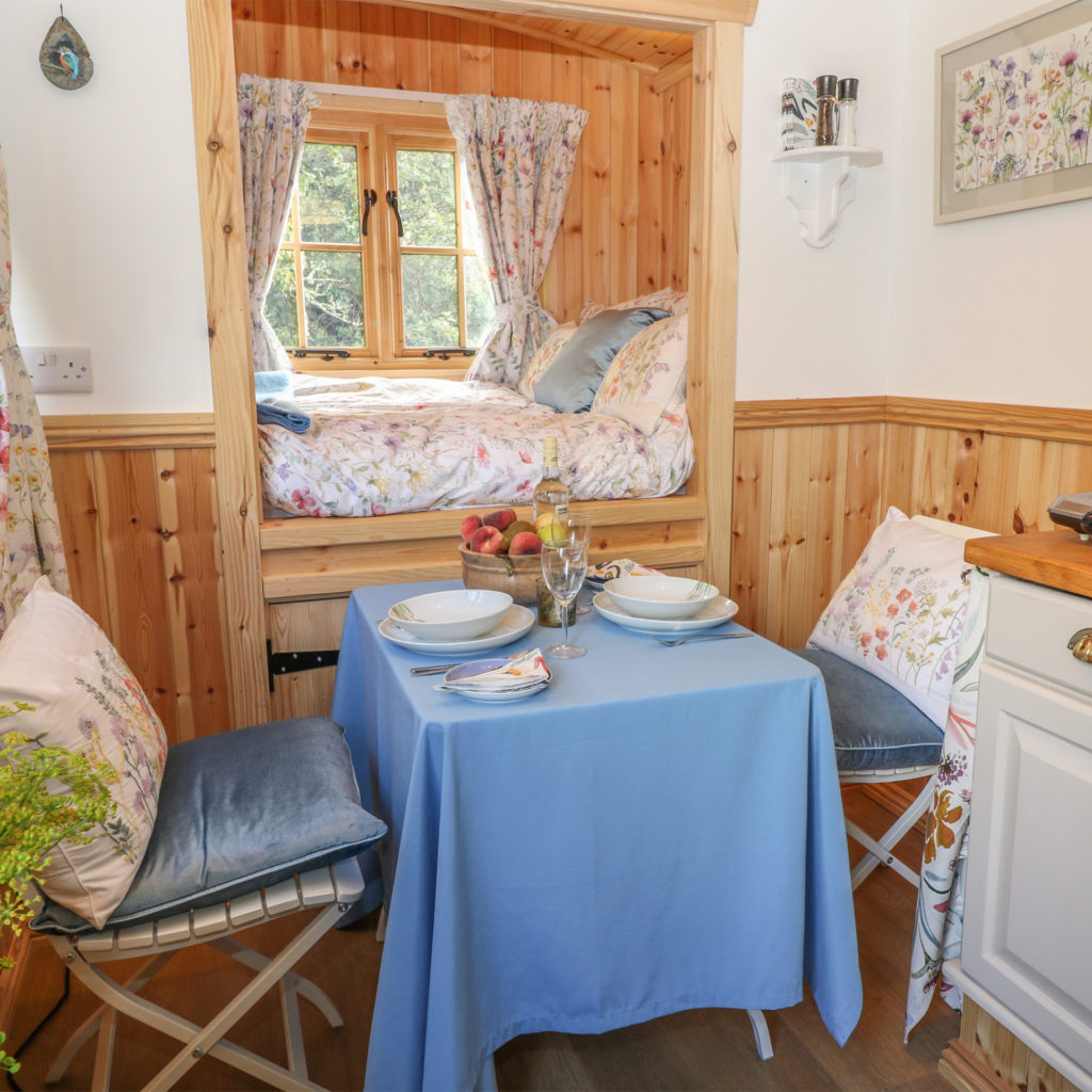 Corner of kitchen unit, tiny table for 2, and truckle bed set into wood panelled wall and window, view over countryside