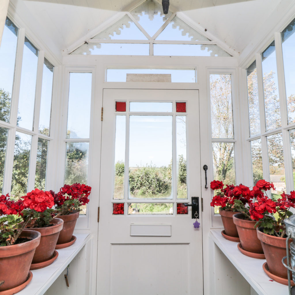 Inside glass cottage porch, pots of red geraniums on shelves, countryside views all around