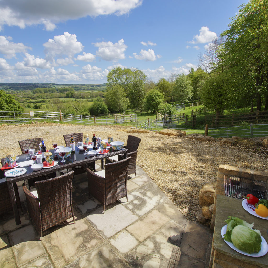 Good quality outdoor furniture, table set for 6 with salad buffet on side, all on wide area of flags and gravel overlooking rolling hills and woods