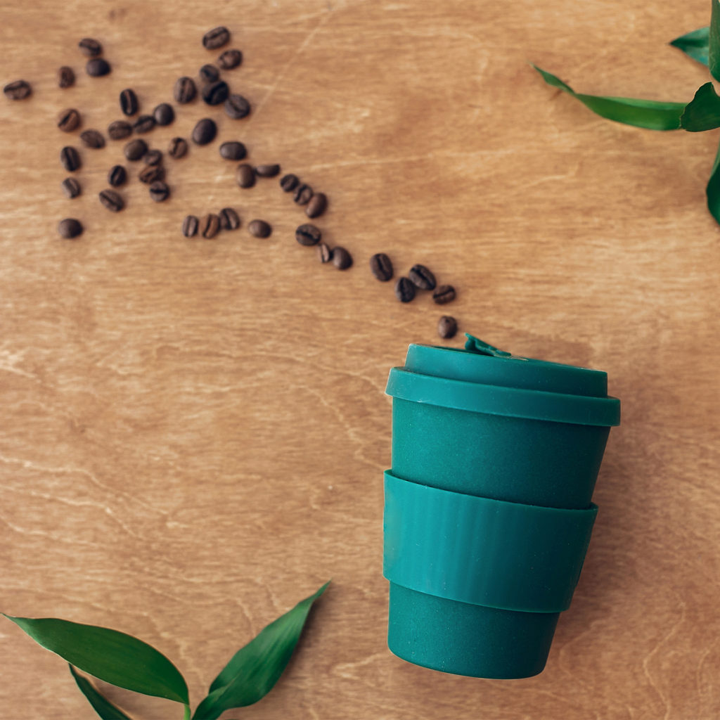 Zero waste concept, flat lay. Stylish reusable eco coffee cup on wooden background with coffee beans and green bamboo leaves. Ban single use plastic. Sustainable lifestyle. Natural bamboo cup