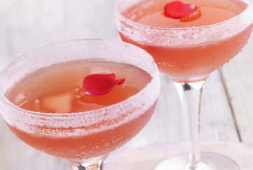 Two sugar-rimmed wide champagne glasses rose wine mocktail, garnished with rose petals