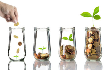 4 glass jars, hand dropping coins into first one, green seedling growing bigger in subsequent jars as level of coins rises
