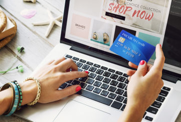Woman's hands, typing on laptop and holding credit card