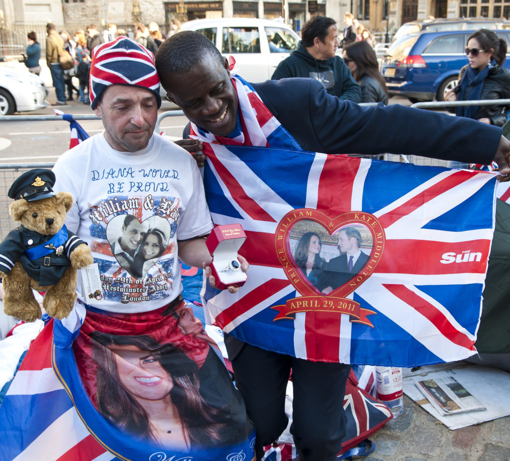 Two men hold up Union Jack flags with a heart shaped picture of William and Kate in the middle, on the street outside Westminster Abbey